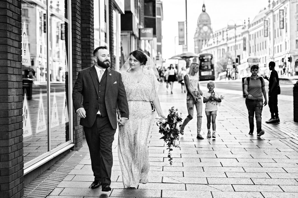 Bride and groom walking through Leeds city centre after their ceremony at Leeds Town Hall