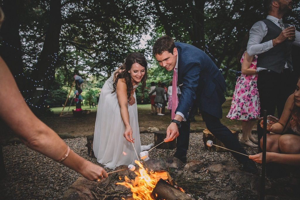 Bride and groom toasting marshmallows at Markington Hall